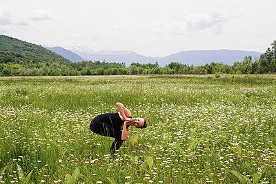 Girl practicing yoga on the mountain plain - p1412m2100836 by Svetlana Shemeleva