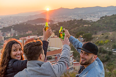 Spain, Barcelona, three happy friends with beer bottles on a hill overlooking the city at sunset - p300m1563250 by VITTA GALLERY