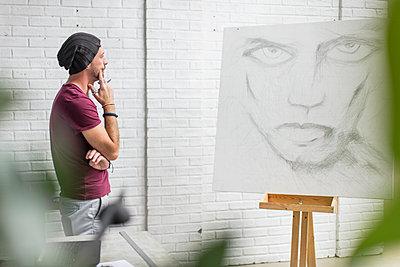 Artist looking at drawing in studio - p300m2013301 von zerocreatives