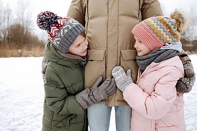 Two smiling siblings together with father in winter - p300m2160076 by Ekaterina Yakunina