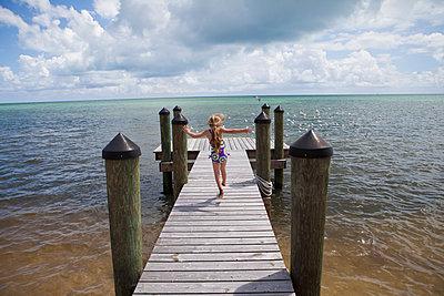 Caucasian girl walking on pier - p555m1480020 by Marc Romanelli