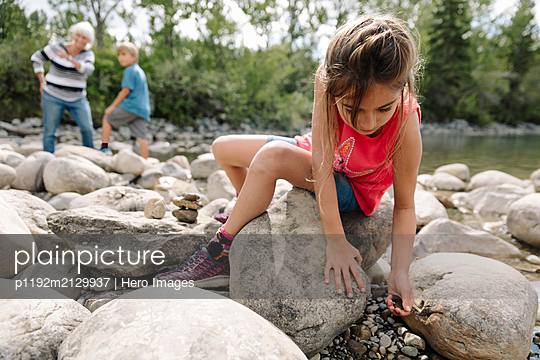 Two children playing on riverbank - p1192m2129937 by Hero Images