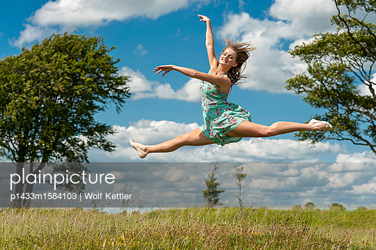 A female ballet dancer performs a grand jeté, the splits in mid-air, as she jumps over a summer meadow - p1433m1584109 by Wolf Kettler