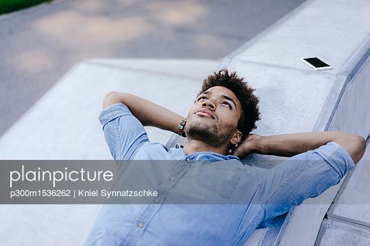 plainpicture | Photo library for authentic images - plainpicture p300m1536262 - Portrait of relaxed man lyi... - plainpicture/Westend61/Kniel Synnatzschke