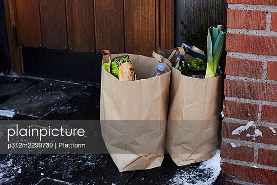 Groceries in paper bags in front of house door - p312m2299739 by Plattform