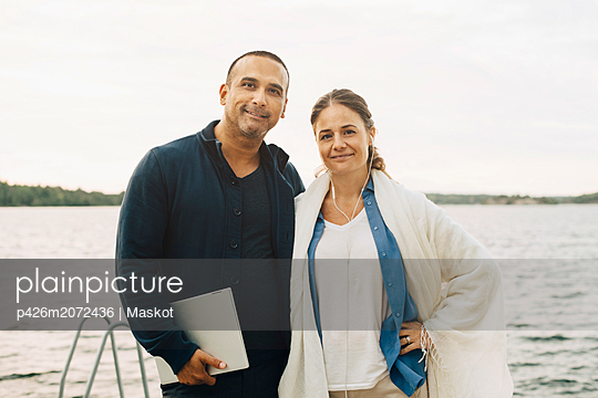 Portrait of smiling mature couple with laptop standing against lake - p426m2072436 by Maskot