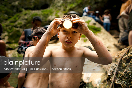 Portrait of young boy wearing a headlamp during an outdoor adventure - p456m1049124 by Jim Erickson / Erickson Stock