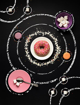 Overhead view of sweet food arranged over galaxy chalk drawing on black background - p1166m1561512 by Cavan Images