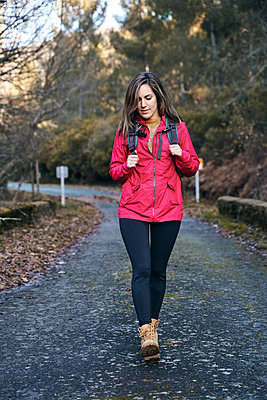 girl with backpack and red jacket walks along a forest path - p1166m2246930 by Cavan Images