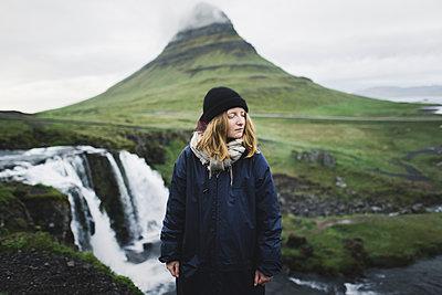 Young woman by Kirkjufell and Kirkjufellsfoss in Iceland - p1427m2123753 by Oleksii Karamanov