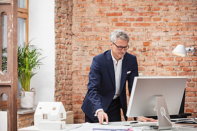 Mature male professional working on computer at desk in work place - p300m2273851 by Studio 27