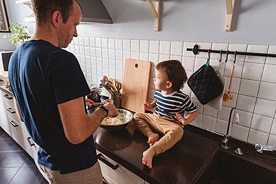 Moskau, Russland. Ein lachender glücklicher Mann mit dem Sohn bereit das Essen auf der Küche vor - p300m2277699 von Katharina und Ekaterina