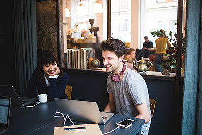 Smiling female and male creative professionals discussing over laptop at desk in office - p426m2089032 by Maskot