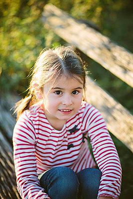 Mädchen sitzt auf einer Parkbank - p946m957553 von Maren Becker