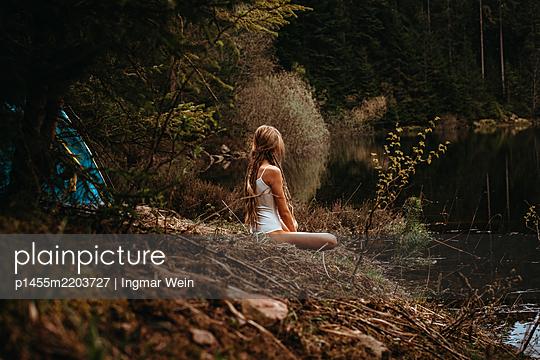 Frau sitzt an einem Bergsee - p1455m2203727 von Ingmar Wein