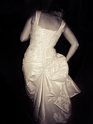 Rear view of Bride in wedding gown at night - p1072m2158341 by Neville Mountford-Hoare