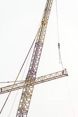 Two construction workers on a crane - p1292m2272661 by Niels Schubert