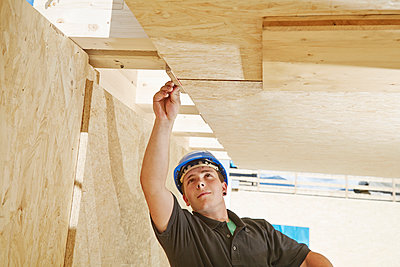 Austria, worker checking roof construction - p300m1567835 by Christian Vorhofer