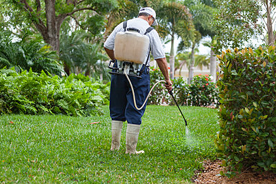 Pest control technician with portable spray rig using  spray nozzle and hose - p442m2154372 by Mark Hunt