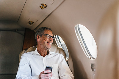 Mature businessman with smartphone in private jet - p586m1208487 by Kniel Synnatzschke