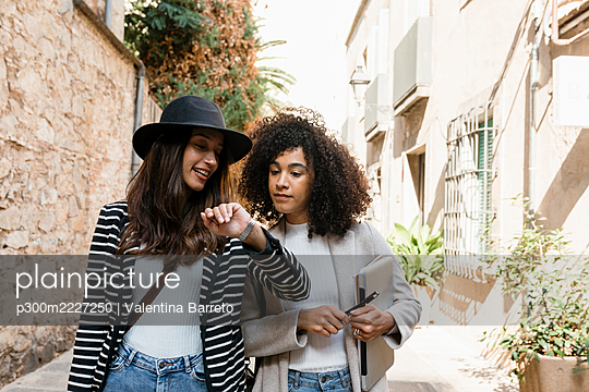 Female entrepreneurs checking time on wristwatch while standing in city during sunny day - p300m2227250 by Valentina Barreto