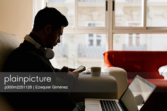 Young man using smart phone while sitting on sofa at home - p300m2251128 by Ezequiel Giménez