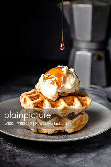 Maple syrup pouring on plate of fresh waffles with ice cream - p300m2293452 by Flavia Morlachetti