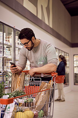 Man text messaging while leaning on shopping cart at refrigerated section in supermarket - p426m1451837 by Maskot