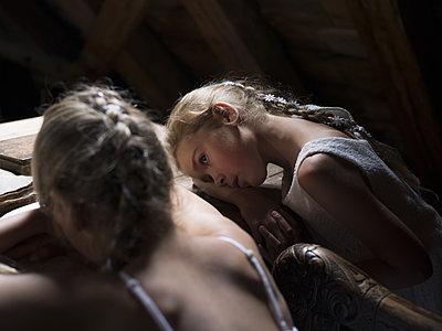 Zwei Mädchen stützen ihre Köpfe auf einen Tisch - p945m1155023 von aurelia frey