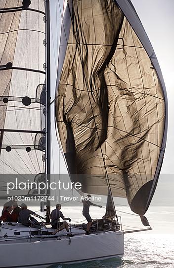 Man adjusting sail on sailboat - p1023m1172744 by Trevor Adeline