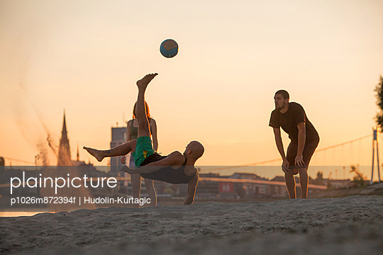 Young people on the beach playing soccer