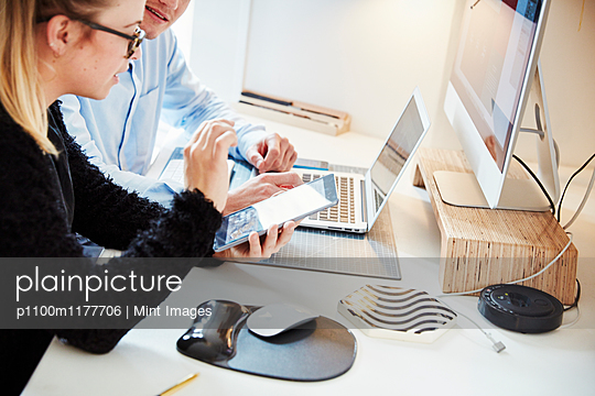 Two people at a workstation, working together on a tablet, laptop computer and screen.  - p1100m1177706 by Mint Images