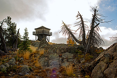 Log cabin on mountain against cloudy sky - p1166m1163721 by Cavan Images