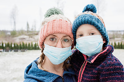 mom and son wearing a face mask as protection from virus and flu - p1166m2171941 by Cavan Images