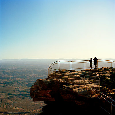 Rear view of couple standing on cliff and looking at view - p1166m968096f by Cavan Images
