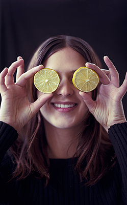 Woman Holding Lemon Slices Over Eyes - p1617m2264083 by Barb McKinney