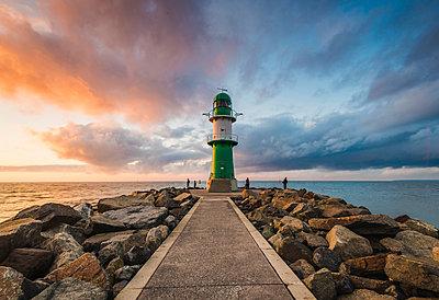 Warnemünde, Rostock district, Baltic coast, Mecklenburg-Western Pomerania, Germany. Pier to the lighthouse at sunset. - p651m2007371 by Marco Bottigelli