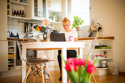 Young woman works on laptop computer in the kitchen - p741m2176781 by Christof Mattes
