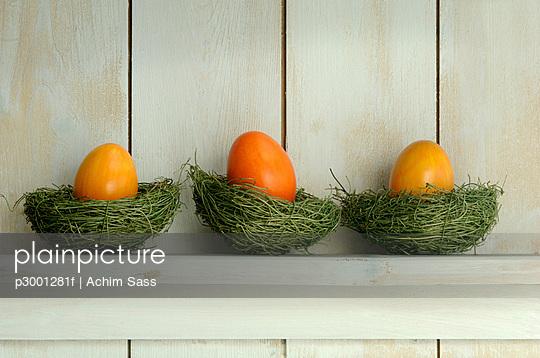 Orange Easter eggs lying on shelf on grass