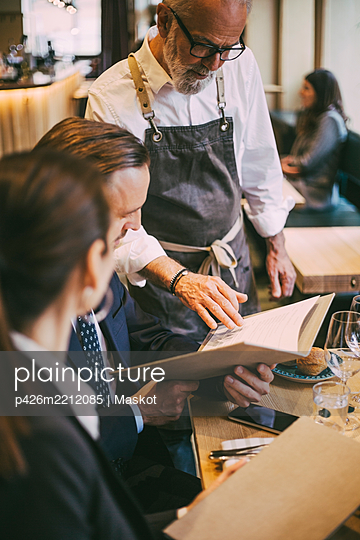 Waiter standing by table while business professionals sitting in restaurant - p426m2212085 by Maskot