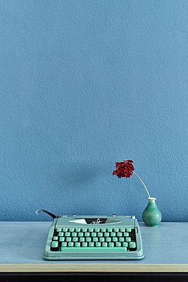 Typewriter in mint colours alongside flower in vase - p1312m2151291 by Axel Killian