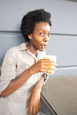 Young African woman has a soft drink - p1640m2260102 by Holly & John