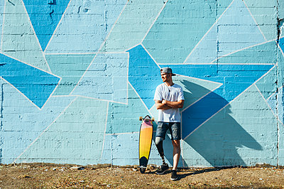 Young man with leg prosthesis standing against concrete wall with a skateboard - p300m2140536 by Jose Luis CARRASCOSA