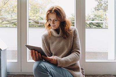 Mature woman sitting on wondow sill, using digital tablet - p300m2155349 by Joseffson