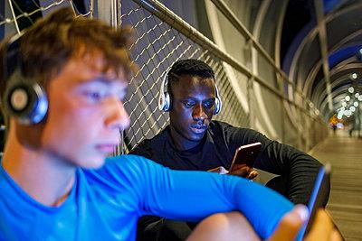Young athletes using smart phones while relaxing on footbridge - p300m2277109 by Ignacio Ferrándiz Roig