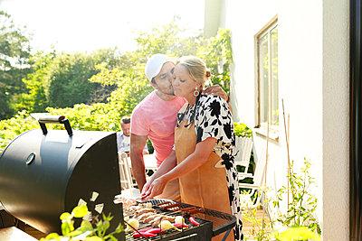 Man kissing woman near barbecue - p312m2237117 by Phia Bergdahl