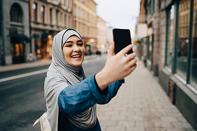 Cheerful young Muslim woman wearing hijab taking selfie on sidewalk in city - p426m1556133 by Maskot