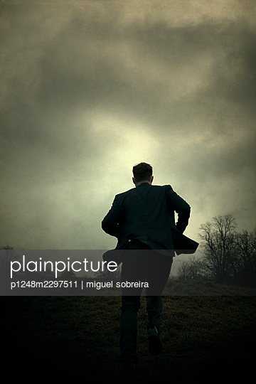 Man in suit running  - p1248m2297511 by miguel sobreira