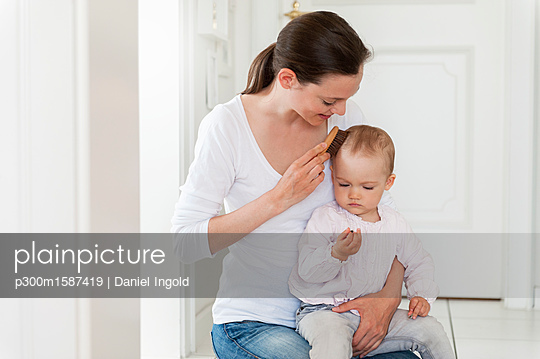 Mother brushing baby's hair at home - p300m1587419 von Daniel Ingold
