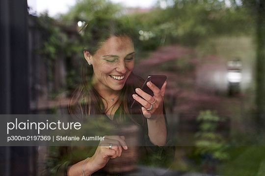 Smiling mid adult woman using mobile phone at home seen through window - p300m2197369 by Stefanie Aumiller
